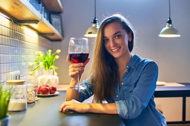 Portrait of beautiful cute young casual smiling happy drinking woman holding a glass of red wine and sitting at the table in the loft style kitchen at home