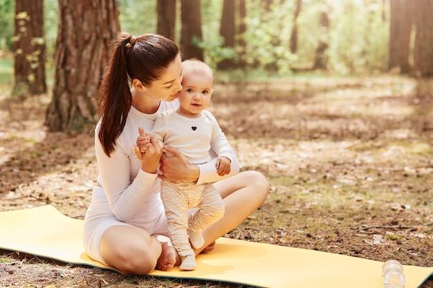 Ritratto di bella donna dai capelli scuri con coda di cavallo seduta con gambe incrociate e abbracciando figlia infantile infant