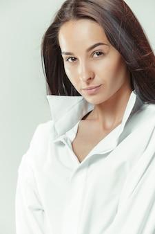 Ritratto di una bella ragazza dai capelli scuri su sfondo grigio studio. moda donna caucasica. ritratto di giovane modella.