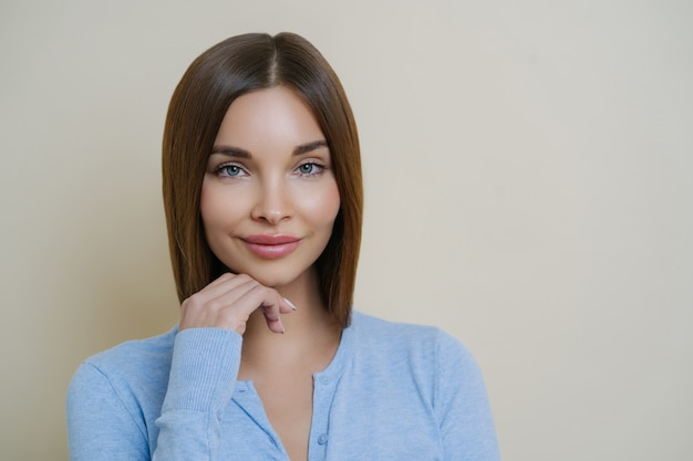 Portrait of beautiful dark haired woman with healthy natural clean skin, touches chin