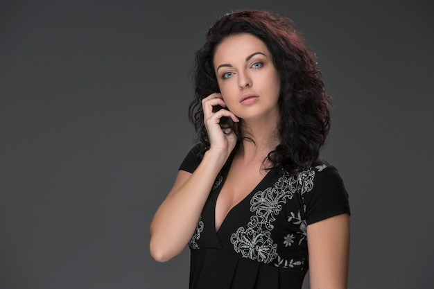 Portrait of beautiful dark-haired young woman, speaking on mobile phone