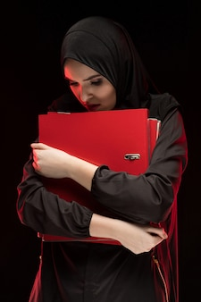 Portrait of beautiful desperate scared frightened young muslim woman wearing black hijab holding folders