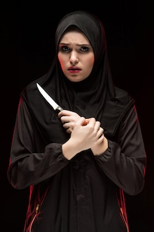 Portrait of beautiful desperate scared frightened young muslim woman wearing black hijab holding knife in her hands