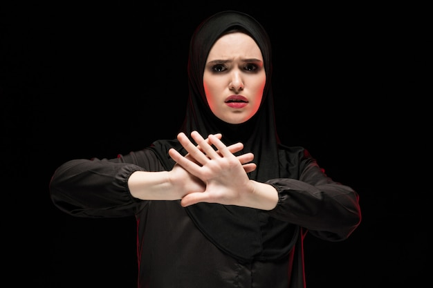 Portrait of beautiful desperate scared frightened young muslim woman wearing black hijab showing stop sign