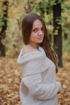 Portrait of a beautiful, dreamy and happy girl with long wavy hair in knit sweater autumn. nice weather