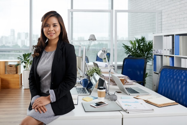 Portrait beautiful elegant business lady sitting on office desk and smiling at camera