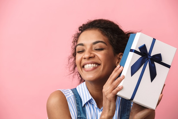 Portrait of a beautiful emotional excited happy young african woman posing isolated over pink wall holding present gift box.