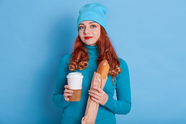 Portrait of beautiful european red haired woman wearing casual sweater and cap