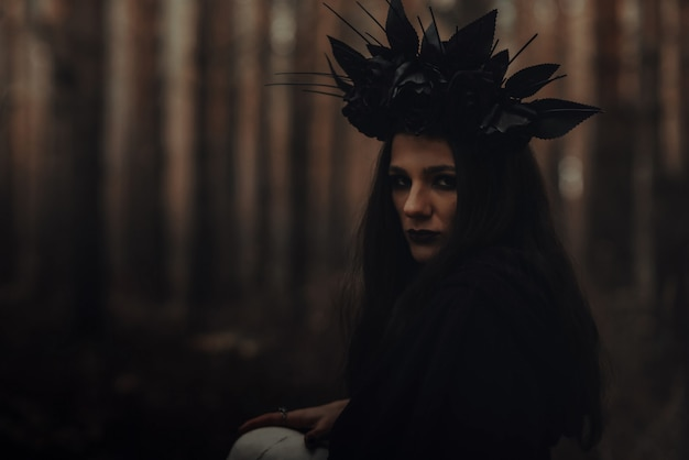 Portrait of a beautiful evil witch sorceress in a dark forest