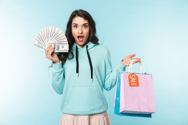 Portrait of a beautiful excited young brunette woman standing over blue, carrying shopping bags, showing money banknotes