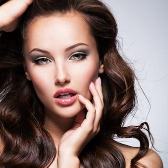 Ritratto della bella donna espressiva con capelli ricci lunghi castani in posa su sfondo scuro