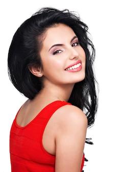Ritratto di bel viso di una giovane donna sorridente in abito rosso