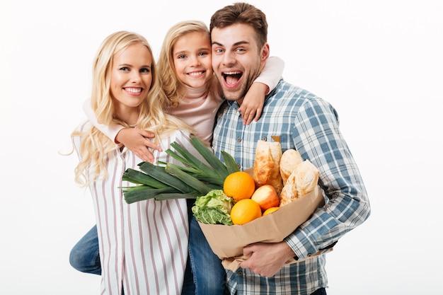 Ritratto di bella famiglia che tiene il sacchetto della spesa di carta