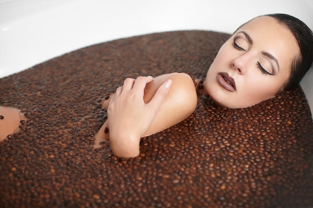 Portrait of beautiful fashion woman in jacuzzi with coffee. body care. bright makeup