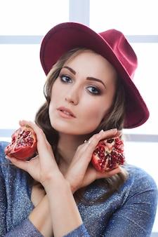 Portrait of beautiful fashion woman with pomegranate fruit