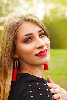 Portrait of a beautiful fashion young women smiling, with red lips, in park, close-up.
