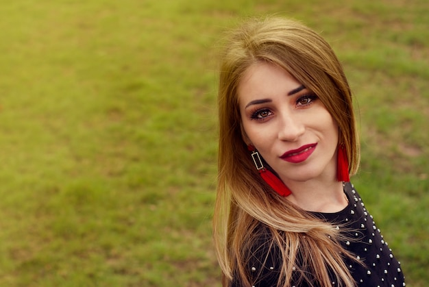 Portrait of a beautiful fashion young women smiling, with red lips, in park, copyspace.