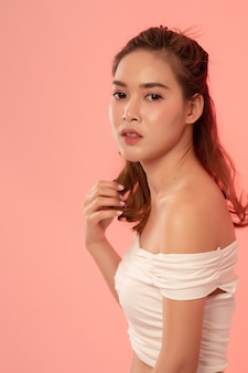 Portrait of beautiful fashionable girl with long hair in a white dress in the studio on a pink. asian model half body look at camera.
