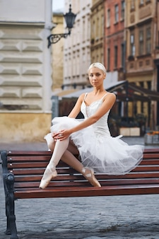 Portrait of a beautiful female ballet dancer resting on the bench in the city center sitting gracefully beauty elegance urban fashion concept.
