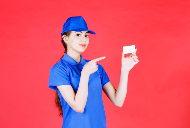 Ritratto di bello corriere femminile che indica biglietto da visita vuoto su colore rosso.