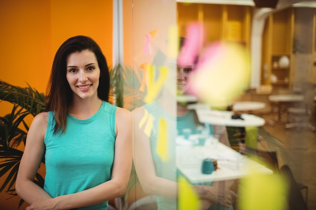 Portrait of beautiful female executive leaning on a glass wall
