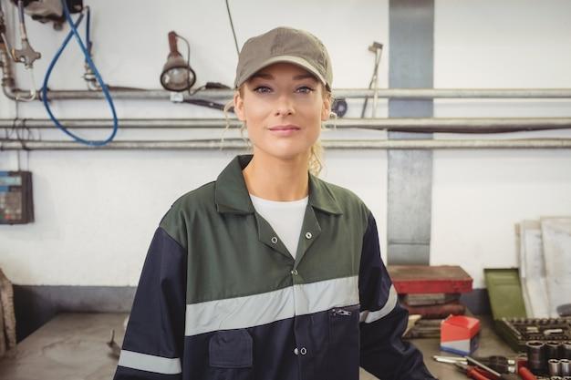 Ritratto di bella donna meccanico in garage