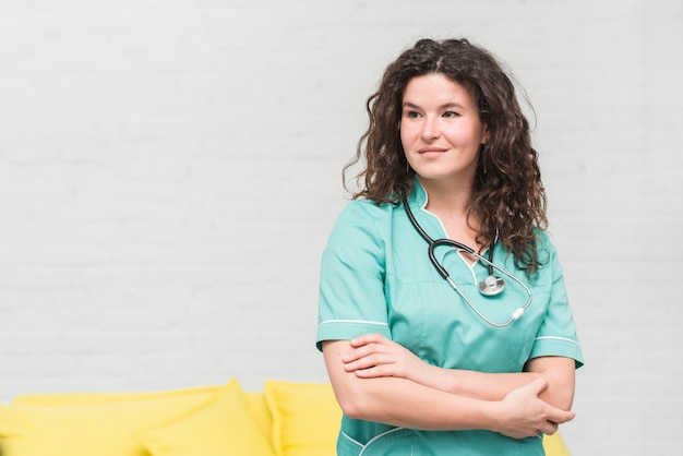 Portrait of beautiful female nurse against white wall