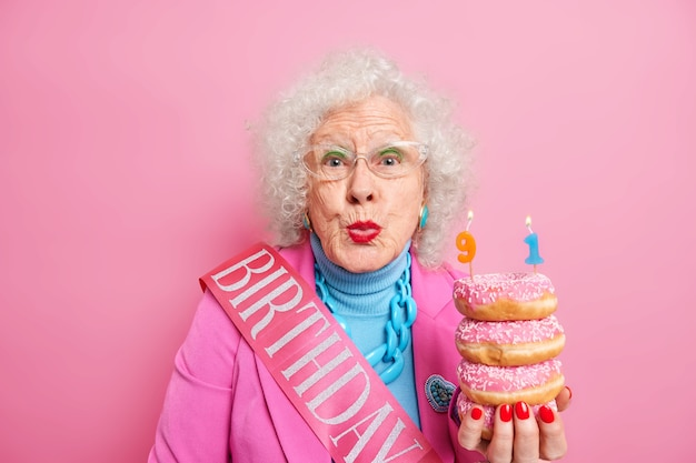Portrait of beautiful female pensioner keeps lips rounded wants to kiss you and says thankful for congratulations being well dressed holds pile of delicious doughnuts