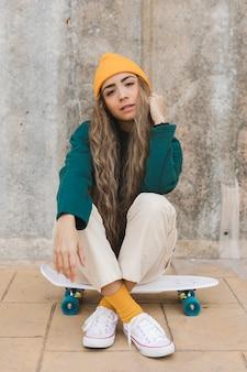 Bella femmina del ritratto che si siede sullo skateboard