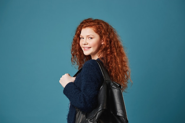 Portrait of beautiful female student with red wavy hair and freckles smiling with teeth, posing for article in school newspaper with backpack.