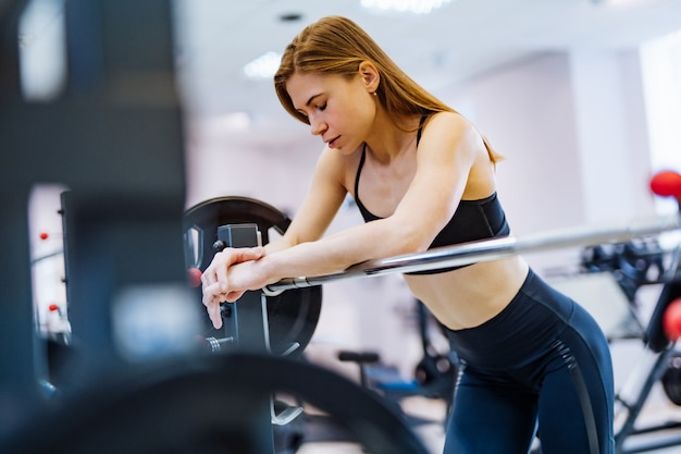 Portrait of beautiful fit woman resting after lifting barbell in fitness centre.