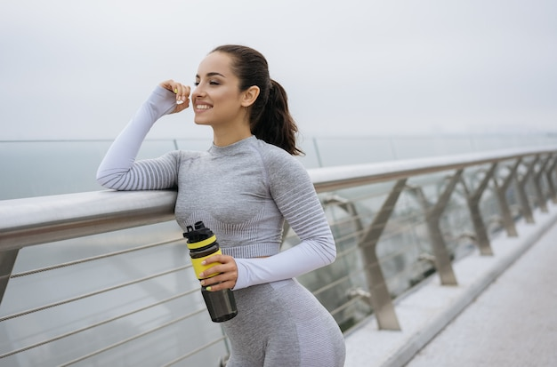 Portrait of beautiful fitness woman in sportswear holding a water bottle, standing outdoors, smiling