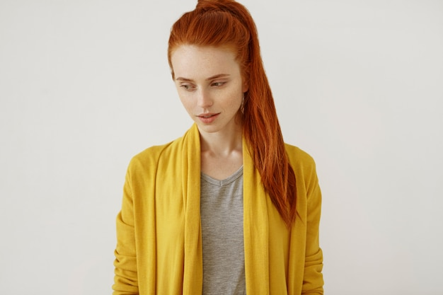 Portrait of beautiful freckled female with ginger pony tail, wearing yellow cape, looking down with thoughtful expression, thinking over something, smiling. red-haired young woman looking down