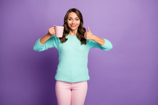 Portrait of beautiful funny curly lady hold hot coffee beverage cup raise thumb finger up approve good taste of drink wear fuzzy pastel sweater pink pants.