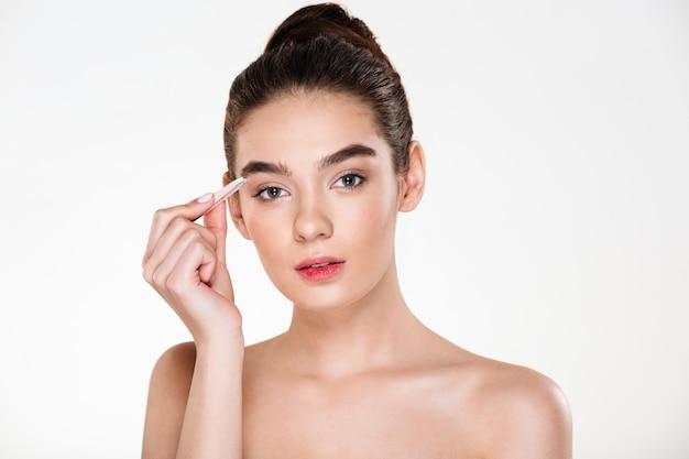 Ritratto di bella donna delicata con pelle pulita depilando le sopracciglia con una pinzetta