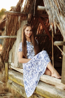 Portrait of a beautiful girl against a wooden house. girl on the background of an old thrown wooden house. girl in white dress with blue embroidery flowers.