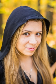 Portrait of beautiful girl as witch dressed in a dress with a hood.