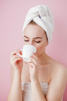 Portrait of beautiful girl in bathrobe with a cup of tea, relaxation concept blonde woman wearing bathrobe and towel on head after shower.