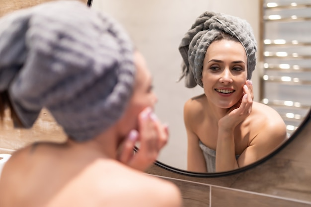 Portrait of beautiful girl in bathrobe and with towel on her head cleaning her face in bathroom