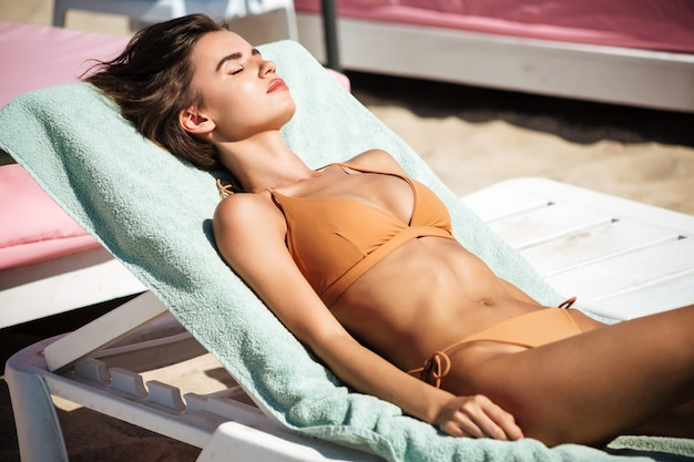 Portrait of beautiful girl in bikini lying on deck chair with closing eyes while spending time on beach. young pretty lady in beige swimsuit sunbathing and relaxing on beach