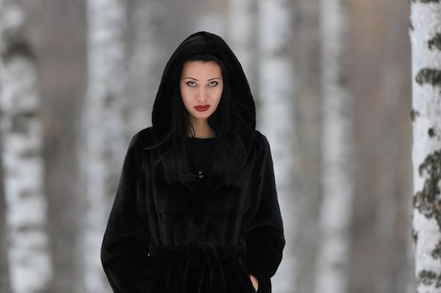Portrait of a beautiful girl in a black mink coat