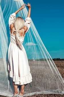 Portrait of a beautiful girl, blonde with long hair in a field, on a background of white transparent fabric