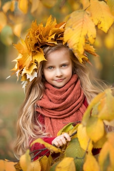 Portrait of a beautiful girl child in autumn leaves