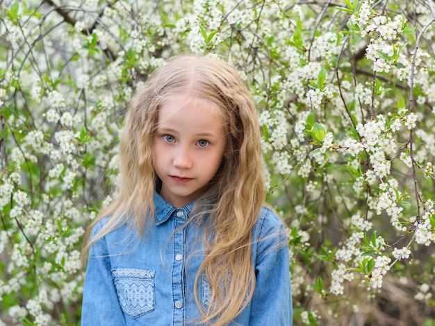 Portrait of a beautiful girl in a denim shirt with a serious facial expression in a cherry orchard.