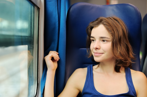 Portrait of a beautiful girl dreaming in a train car