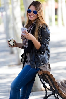 Portrait of beautiful girl drinking coffee and using her mobile