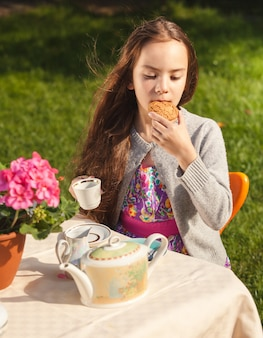 Portrait of beautiful girl having breakfast at yard and biting cookie