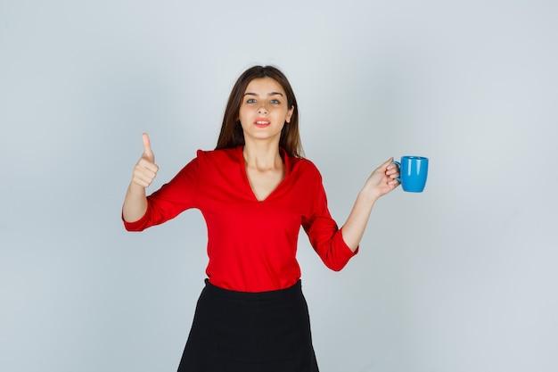 Ritratto di bella ragazza che tiene tazza, mostrando pollice in camicetta rossa, gonna nera e guardando pensieroso, vista frontale.