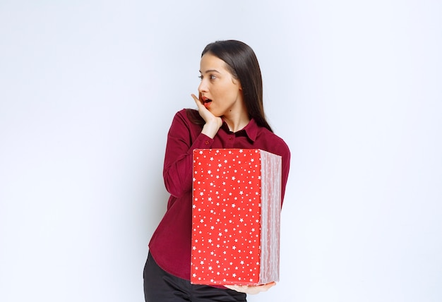 Portrait of a beautiful girl holding present box and looking away over white wall .