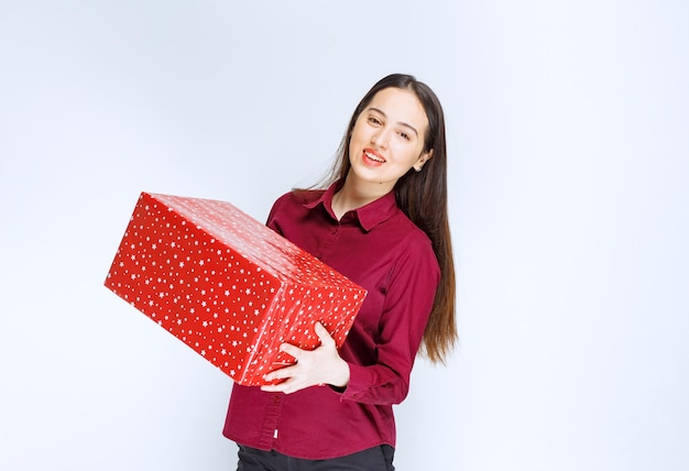 Portrait of a beautiful girl holding present box  over white wall .